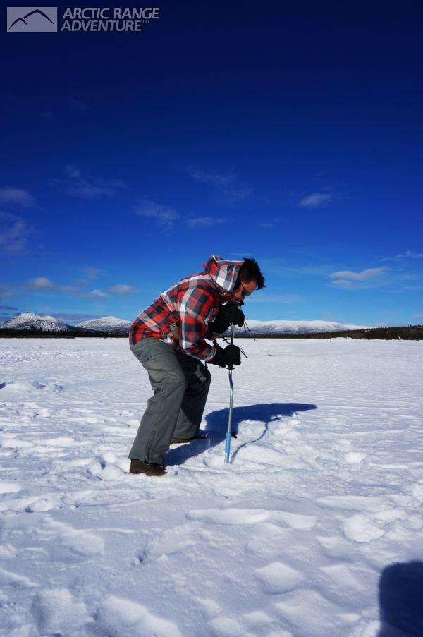 Drilling the fishing hole ice fishing arctic range for Ice fishing hole